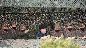 North Korea's Kim shows no panic appearing WITHOUT protective gear, surrounded by ALL-MASKED officers during military drills