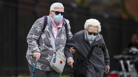 Elderly members of the public wearing face masks walk down a street in Central London on April 01, 2020 in London, England
