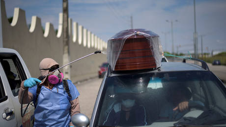 A worker sprays disinfectant on a vehicle carrying a coffin lined up to enter a cemetery, in Guayaquil, Ecuador April 2, 2020.