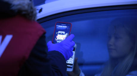An employee scans the smart ticket at a drive-in cinema in Essen, western Germany, on March 29, 2020