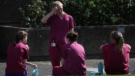Medical staff at St Thomas' Hospital relax during a break in London, Britain, April 6, 2020. © REUTERS/Hannah McKay