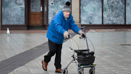 An elderly man pushes a mobility walker in front of a closed down shop in Cardiff City centre on March 17, 2020 in Cardiff, Wales. ©  Getty images / Matthew Horwood