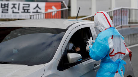 A medical staff member in protective gear tests a patient in Daegu, South Korea during the initial Covid-19 outbreak, March 3, 2020.