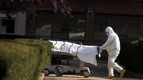 FILE PHOTO: A healthcare worker wheels the body of deceased people from a Brooklyn hospital during the coronavirus outbreak in New York City.