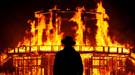 """A Burning Man Ranger guards near the the effigy of """"The Man"""" in Black Rock, Nevada, US September 2, 2017"""