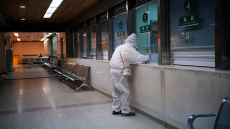 FILE PHOTO. A woman wearing protective suit is seen at a hospital after the lockdown was lifted in Wuhan.