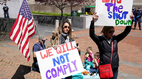 FILE PHOTO: Protesters hold signs in opposition to Virginia's stay-at-home order, part of a growing number of residents across several states demanding an end to lockdown measures.
