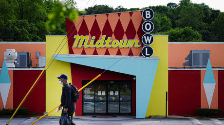 FILE PHOTO: A man walks past a bowling alley in Atlanta, Georgia days before the phased repeal of lockdown measures imposed to halt the spread of Covid-19.