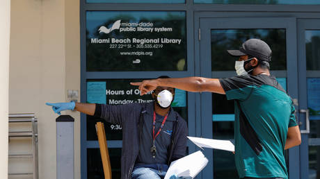 A man speaks with a library worker after receiving an unemployment form, as the outbreak of COVID-19 continues, in Miami Beach, Florida, US