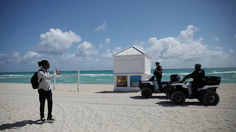 Police officers ask a man to leave beach for precaution due to coronavirus spread, in Miami Beach, Florida, US