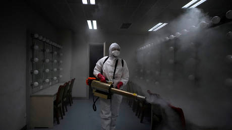 FILE PHOTO A volunteer disinfects the Qintai Grand Theatre in Wuhan, China. April 2020. © Reuters / Aly Song