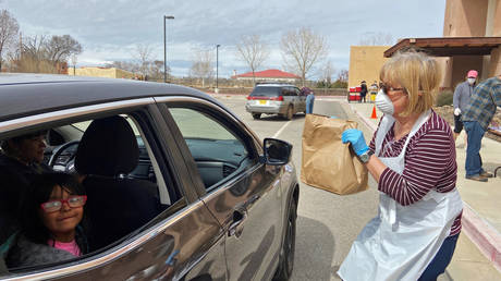 FILE PHOTO: Volunteers hand out free groceries at a drive-by aid station, providing food to families and children in New Mexico during the Covid-19 crisis.