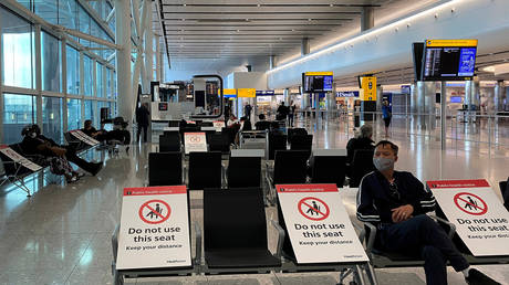 People sit amongst socially-distanced seating signs at Heathrow Airport, London, Britain on May 10, 2020.