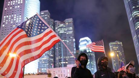A protestor holds a US flag in Hong Kong, China, November 28, 2019.