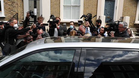 Media members surround a car Dominic Cummings is in as he leaves his house in London on Sunday. © REUTERS/Simon Dawson