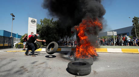 Nissan worker throws a tire on a burning pile during a protest in front of the Barcelona factory against the possible closure of the plant.