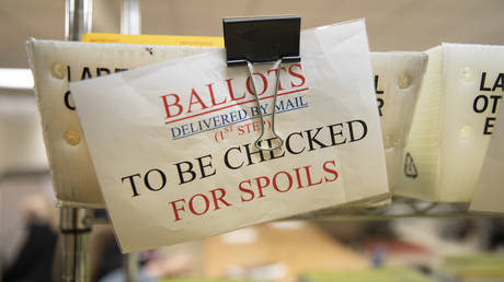 Mailed in ballots sit in US Postal Service bins inside the office of the Stanislaus County Clerk
