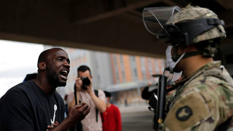 A man confronts a National Guard soldier in Minneapolis, Minnesota as journalists take photos, May 29, 2020.