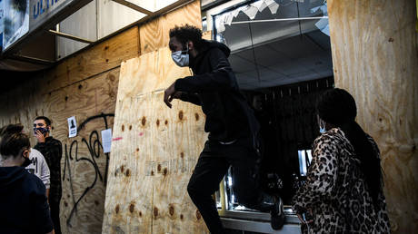 A protestor jumps out of a window of a convenience store as it is looted during a demonstration in Minneapolis, Minnesota, on May 29, 2020 © AFP / CHANDAN KHANNA