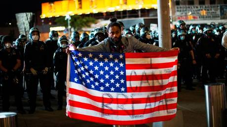 A protester holds a U.S. flag in front of NYPD police officers in New York City © REUTERS/Eduardo Munoz