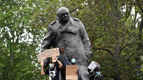 """People gesture and hold banners on the Winston Churchill statue during a""""Black Lives Matter in London"""