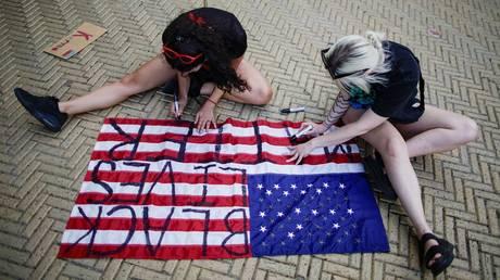Demonstrators write Black Lives Matter on a US flag during George Floyd protests in New York City. © Reuters / Eduardo Munoz