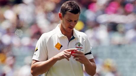 Australia's Josh Hazlewood shines the ball