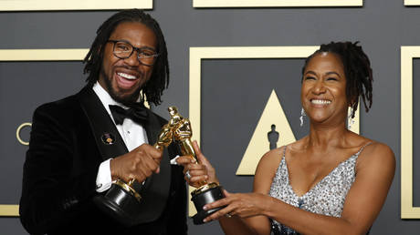 """Matthew A. Cherry and Karen Rupert Toliver pose with the Oscar for Best Animated Short Film for """"Hair Love,"""" at the 92nd Academy Awards in Hollywood, February 9, 2020."""