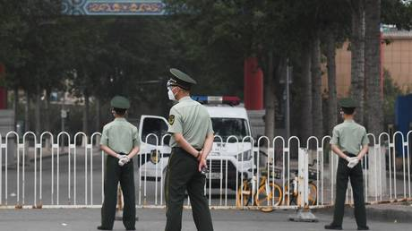 Paramilitary police officers stand guard at an entrance to the closed Xinfadi market in Beijing on June 13, 2020. © AFP / Greg Baker