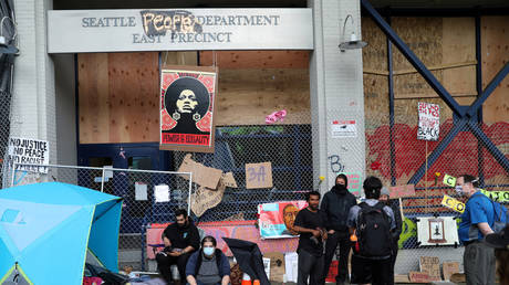 FILE PHOTO: Protesters hang around an entrance of the Seattle Police Department East Precinct at the self-proclaimed Capitol Hill Autonomous Zone (CHAZ), in Seattle, Washington.