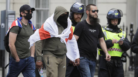 Protesters walk past British police officers in central London as groups, including those from the far-right, gathered to counter-protest against anti-Racism demonstrators, Saturday, June 13, 2020. © AP Photo/Kirsty Wigglesworth