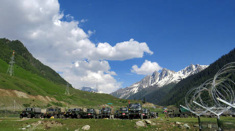 Indian army soldiers walk past their parked trucks at a makeshift transit camp before heading to Ladakh, near Baltal, southeast of Srinagar, June 16, 2020