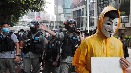 FILE PHOTO: Riot police ask pro-democracy demonstrators in Hong Kong to leave as they attend a vigil for a protester who fell to his death during a demonstration last year.