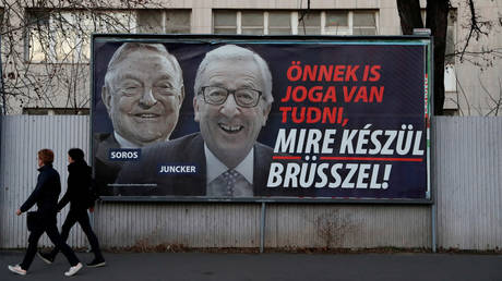 FILE PHOTO: A Hungary government billboard accusing then-European Commission President Jean-Claude Juncker of pushing migration plans encouraged by George Soros. ©REUTERS/Bernadett Szabo