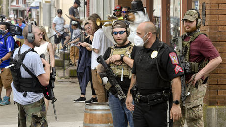 Three men carrying rifles who stood along Philadelphia Ave during the protest, talk with an Eastern Berks Regional Police Officer, June 2, 2020