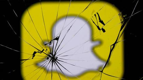 Snapchat logo is seen through broken glass