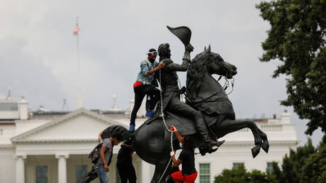 Protesters attach a chain to the statue of US President Andrew Jackson in front of the White House in an attempt to pull it down, June 22, 2020