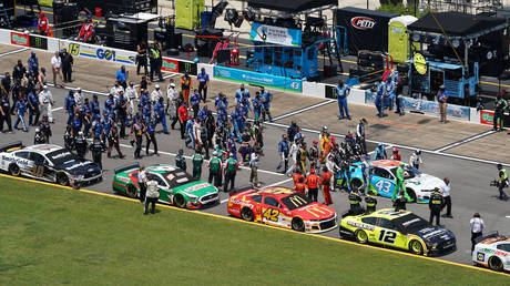 NASCAR drivers push the car of NASCAR Cup Series driver Bubba Wallace (43) to the front of the grid on pit road before the Geico 500 at Talladega Superspeedway