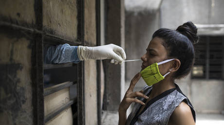 A health official collects a swab sample from a woman at a free testing facility in New Delhi, June 19, 2020 © AFP / XAVIER GALIANA
