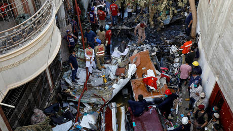 Rescue workers gather at the site of a passenger plane crash in a residential area near an airport in Karachi, Pakistan May 22, 2020. © Akhtar Soomro/Reuters