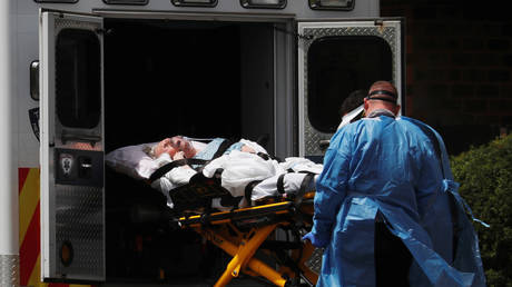 FILE PHOTO: EMTs load a patient into an ambulance outside a clinic in Hammonton, New Jersey.