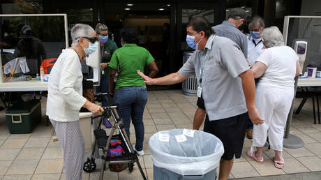 People wait for a health assessment before entering Jackson Memorial Hospital in Miami, Florida