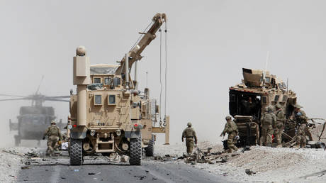 FILE PHOTO. US troops assess the damage to an armored vehicle of NATO-led military coalition after a suicide attack in Kandahar province, Afghanistan.