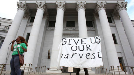 DonQuenick demands reparations and a protester raises a sign reading 'Give us our harvest' in front of a crowd of concerned citizens who gathered at the steps of Denver City Hall in Denver, Colorado, U.S., June 29, 2020