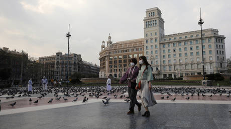 FILE PHOTO. Women in face masks walk through an empty Plaza de Catalunya in Barcelona. ©REUTERS / Nacho Doce