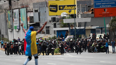 FILE PHOTO: A demonstrator covered with a Venezuelan flag gestures in front of the security forces during a protest in Caracas, Venezuela March 10, 2020 © REUTERS/Carlos Jasso