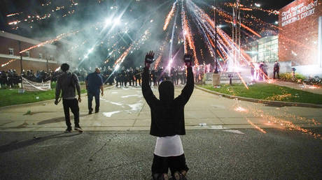 Fireworks explodes over a protestor with his hands up during a protest in Ferguson, Missouri, May 30, 2020.