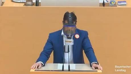 An alternative for Germany MP Stefan Loew speaks while wearing a gas mask © Bavarian State Parliament