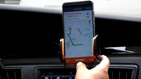 A Didi Chuxing driver checks the information on the application in his car in Beijing, China