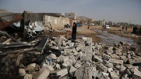 A woman stands near the wreckage of a store of truck oil and tyres after it was targeted by airstrikes carried out by the Saudi-led coalition on July 02, 2020 in Sana'a, Yemen